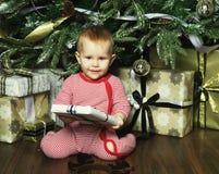 Pequeño bebé con la Navidad de adornamiento cercana tr de la caja de regalo Foto de archivo libre de regalías