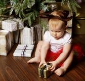 Pequeño bebé con la Navidad de adornamiento cercana tr de la caja de regalo Fotografía de archivo libre de regalías