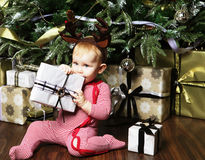 Pequeño bebé con la Navidad de adornamiento cercana tr de la caja de regalo Foto de archivo