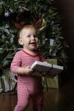 Pequeño bebé con la Navidad de adornamiento cercana tr de la caja de regalo Fotos de archivo