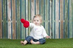 Pequeño bebé con la pequeña almohada roja del corazón Fotografía de archivo