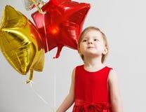 Pequeño bebé con los globos brillantes coloridos de la hoja Fotografía de archivo