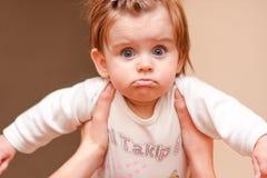 Pequeño bebé con los ojos azules en la casa Foto de archivo
