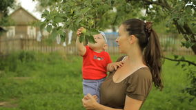 Pequeño bebé con su juego joven de la madre con el manzano almacen de video
