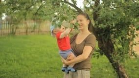 Pequeño bebé con su juego joven de la madre con el manzano metrajes