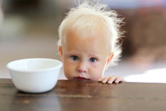 Pequeño bebé de un año triste con el cuenco de cereal vacío Fotografía de archivo