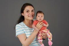 Pequeño bebé del control joven de la mamá fotos de archivo