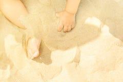 Pequeño bebé del niño que juega en la playa por el mar Pequeños pies de las manos en arena Día de verano asoleado Caridad del Par foto de archivo libre de regalías