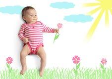 Pequeño bebé divertido con la flor exhausta Foto de archivo libre de regalías
