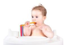 Pequeño bebé divertido en una trona que sostiene una cuchara Imagenes de archivo
