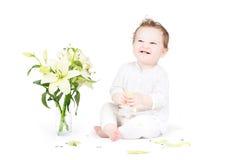 Pequeño bebé divertido que juega con las flores del lirio Foto de archivo