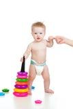 Pequeño bebé divertido que se coloca con la ayuda de la madre fotos de archivo