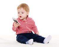 Pequeño bebé dulce con el teléfono móvil Imagenes de archivo
