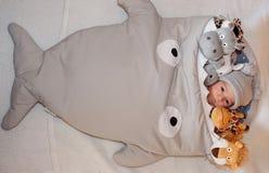 Pequeño bebé dulce que miente en la cama rodeada de peluches lindos del safari Imágenes de archivo libres de regalías
