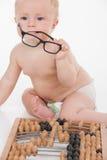 Pequeño bebé elegante divertido que sostiene los vidrios y que se sienta por el ábaco. imagen de archivo libre de regalías