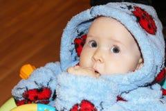 Pequeño bebé en bata con vista sorprendente fotografía de archivo