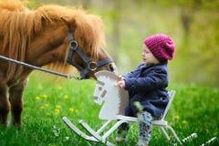 Pequeño bebé en caballo mecedora y potro de madera Foto de archivo