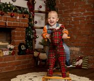 Pequeño bebé en el caballo mecedora, vestido en suéter y vaqueros Decoraciones de la Navidad o del Año Nuevo Fotos de archivo