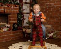 Pequeño bebé en el caballo mecedora, vestido en suéter y vaqueros Decoraciones de la Navidad o del Año Nuevo Foto de archivo
