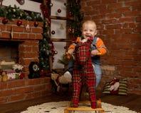 Pequeño bebé en el caballo mecedora, vestido en suéter y vaqueros Decoraciones de la Navidad o del Año Nuevo Imagen de archivo libre de regalías