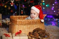 Pequeño bebé en el sombrero de Papá Noel que se sienta en una cesta de mimbre Imagen de archivo libre de regalías