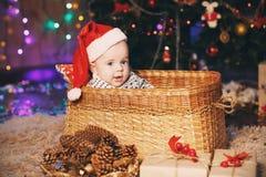 Pequeño bebé en el sombrero de Papá Noel que se sienta en una cesta de mimbre Fotos de archivo