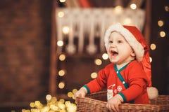 Pequeño bebé en el sombrero de Papá Noel que se sienta en una cesta de mimbre Imagenes de archivo