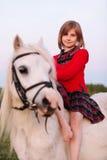 Pequeño bebé en el vestido que se sienta de lado en un caballo blanco Foto de archivo libre de regalías