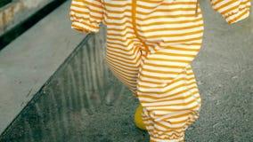 Pequeño bebé en impermeable impermeable rayado anaranjado y paseos de goma amarillos de las botas de lluvia en charcos después de almacen de metraje de vídeo