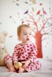 Pequeño bebé en la cama que desgasta los pijamas rojos Foto de archivo libre de regalías