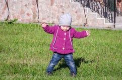 Pequeño bebé en la chaqueta y el sombrero de los vaqueros que hacen el aprendizaje caminar sus primeros pasos en el césped en la  Foto de archivo