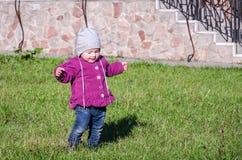 Pequeño bebé en la chaqueta y el sombrero de los vaqueros que hacen el aprendizaje caminar sus primeros pasos en el césped en la  Foto de archivo libre de regalías