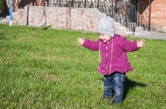 Pequeño bebé en la chaqueta y el sombrero de los vaqueros que hacen el aprendizaje caminar sus primeros pasos en el césped en la  Fotografía de archivo