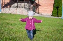 Pequeño bebé en la chaqueta y el sombrero de los vaqueros que hacen el aprendizaje caminar sus primeros pasos en el césped en la  Imagen de archivo libre de regalías