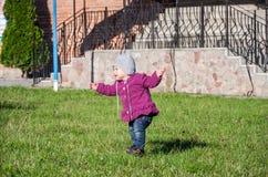 Pequeño bebé en la chaqueta y el sombrero de los vaqueros que hacen el aprendizaje caminar sus primeros pasos en el césped en la  Imagen de archivo