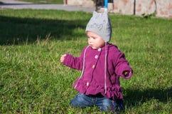 Pequeño bebé en la chaqueta y el sombrero de los vaqueros que hacen el aprendizaje caminar sus primeros pasos en el césped en la  Imagenes de archivo