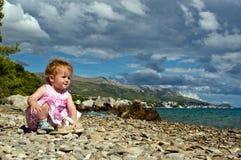 Pequeño bebé en la playa de Adriático. Foto de archivo