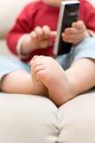 Pequeño bebé en llamada del sofá por el teléfono Foto de archivo