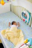 Pequeño bebé en pesebre grande Imagenes de archivo