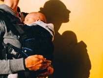 Pequeño bebé en portador y madre con el premio en fondo amarillo foto de archivo