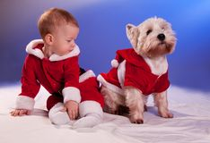 Pequeño bebé en Santa Claus y perro en el traje de Santa Claus foto de archivo libre de regalías