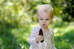 Pequeño bebé en un bosque que sostiene un cono imagen de archivo
