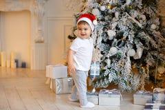 Pequeño bebé encantador en el sombrero de Papá Noel y la ropa de color claro Imágenes de archivo libres de regalías