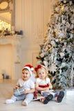 Pequeño bebé encantador en los sombreros rojos de Papá Noel y el pequeño g rubio fotografía de archivo libre de regalías