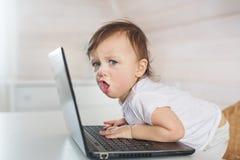 Pequeño bebé enojado con un ordenador portátil Imagen de archivo