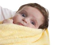 Pequeño bebé envuelto en una toalla amarilla Fotos de archivo