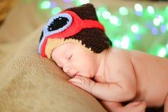 Pequeño bebé europeo que lleva el casquillo marrón y que miente en fondo de los resplandores foto de archivo libre de regalías