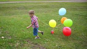 Pequeño bebé feliz, diversión que corre alrededor con los globos Reconstrucción al aire libre Celebración y diversión Cumpleaños  almacen de metraje de vídeo