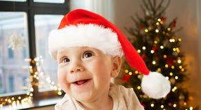 Pequeño bebé feliz en el sombrero de santa en la Navidad imagen de archivo