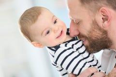 Pequeño bebé feliz en los brazos del padre feliz Imagen de archivo